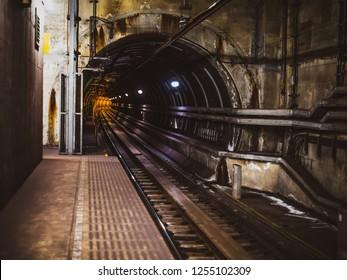 Dark subway tunnel with yellow light of train coming , Japan subway in Osaka city