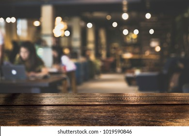 Dark Table top Counter with blurred of coffee shop or modern library . Abstract, freelancer working on laptop in cafe with a cup of coffee.