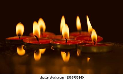 Dark tealight candle flame burn