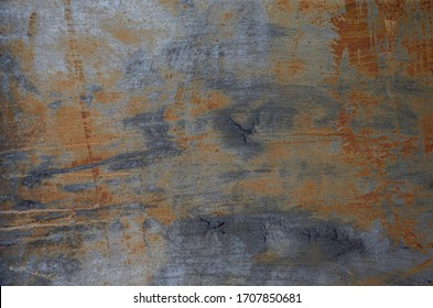 Dark textured painted cracked multicoloured rusty aged metal background.
