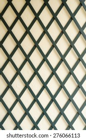 dark thin wooden boards forming a regular diamond pattern in front of a bright cement wall.