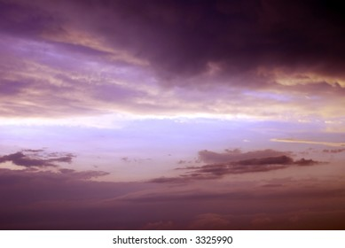 A dark and threatening purple sky during a spring thunderstorm with a blue sky opening in the center