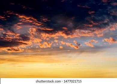 Dark thunderclouds with red orange reflections of the setting sun. Scenic storm clouds lit by the last rays of the sunset. Dramatic  skyscape at sunset. Moody sky at evening.