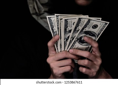 Dark tone picture with select focus of woman in balaclava with money ,Outlaw womanin black hood holding money for sell drug