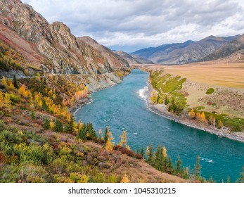 Dark turquoise flow of Katun River and surrounding mountains along the Chuysky Trakt road in the Altai Mountains region of Siberia. Yellow larches and other autumn trees in front on a cloudy day.
