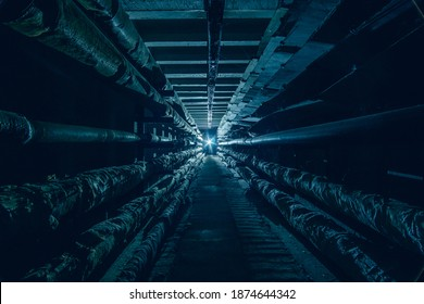 Dark underground concrete utility communication tunnel with pipes and wires in cold colors.