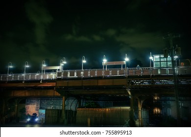 Dark urban Chicago city scene at night with an elevated train platform, person, car and alley.