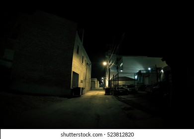 Dark urban city alley at night with fence, cars and parking lot
