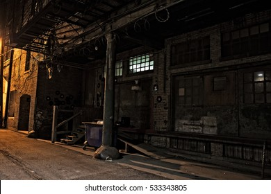 Dark urban city alley at night with loading dock and dumpster. Interesting d�©cor with vinyl records, dress and barb wire.