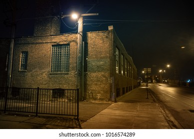 Dark urban city street and alleyway corner with an industrial warehouse factory and an urban road leading to a vintage bridge in Chicago at night.