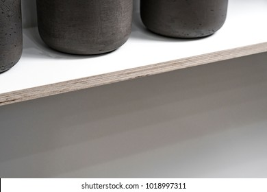 Dark vases lined up on a plywood shelf.