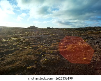 Dark volcanic gravel landscape with moss in Iceland. Backplate for 4x4 4WD offroad cars. Backplate for trekking and hiking. Big lense flare.