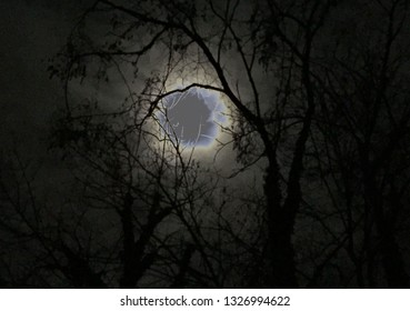A dark West Virginia night yields a small window beyond the clouds allowing the moonlight to peek through to the earth beneath it.