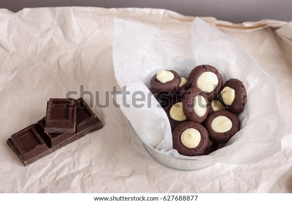 Dark and white chocolate cookies with in metal bowl on light backdrop. Tasty and fresh sweet with filling. Pieces of chocolate on table