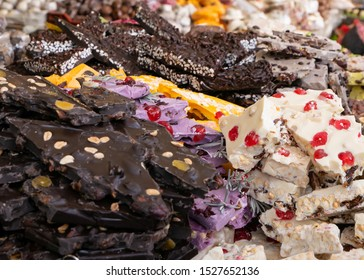 Dark, white and colors chocolate pieces crushed and cocoa beans, culinary background