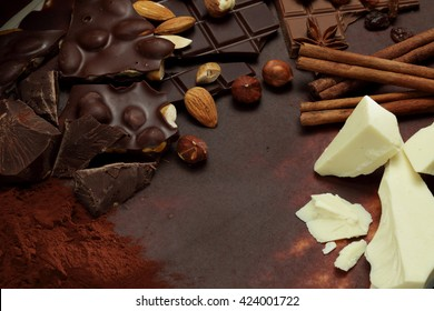 Dark,  white and  nut chocolate background, hazelnuts and almonds on cocoa powder