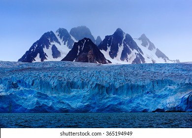 Dark winter mountain with snow, blue glacier ice with sea in the foreground, Svalbard, Norway.