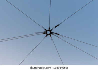dark wires are connected at one point against the blue sky. communication wires diverge in different directions