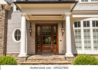 dark wood stained custom door with windows outside of a large custom home with columns and windows
