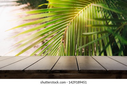 Dark wood table top (Bar) with blur on green palm leaves or tree in tropical forest or jungle with bokeh light at background - Using for Mock up template for display of your design.