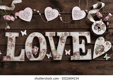 dark wooden background with vintage style letters LOVE and decoration made with decoupage technique