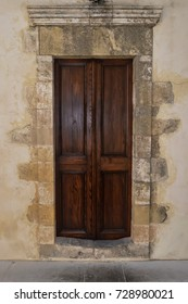 A dark wooden door on a stony wall with a sculpture.