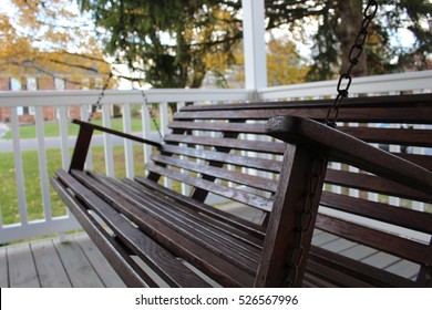 Dark wooden front porch swing on gray and white porch railing