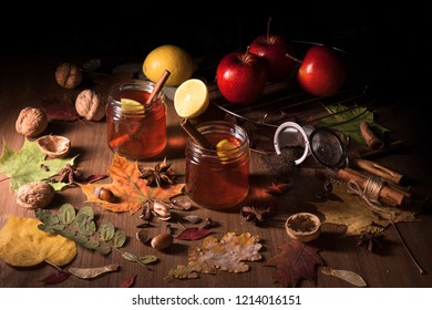 Dark wooden table with 2 glasses of tee with fall, autumn decoration and dark, black background. Colourful leaves, lemon, cinnamon, wallnuts, apples, tea, wallnut shells, hazelnuts, strainer, acorns.