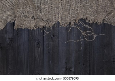 Dark wooden table background with burlap, top view