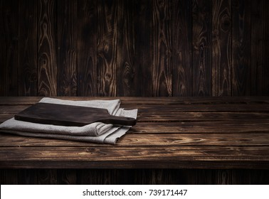 Dark wooden table for product, brown wooden perspective interior with old cutting board