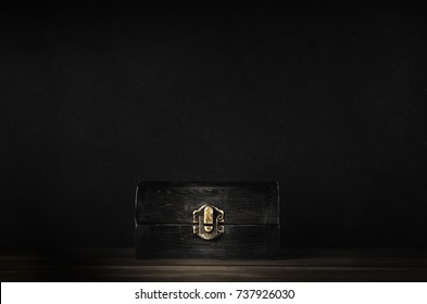 A dark wooden treasure chest with lid closed  by metal clasp on planked surface with black chalkboard background.