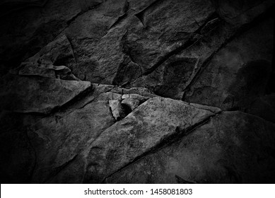 Darkened abstract background of a black rock wall
