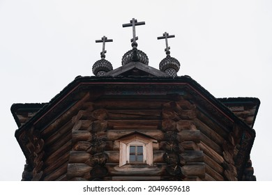 A darkened blockhouse with domes, three crosses and ornaments on the roof. Ancient wooden church building with a window under the roof