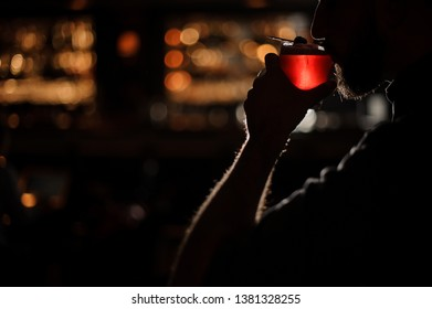 Darkened shot of a young bartender with beard sipping alcohol drink from behind