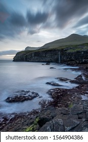 A darkened sky casts an imposing moody view over the coastline of the Faroe Islands and contrasts with the white smooth waves gliding over the rocks.