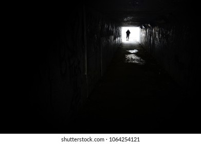 A darkened underground tunnel with a man emerging at the end of the lightened path. blurr