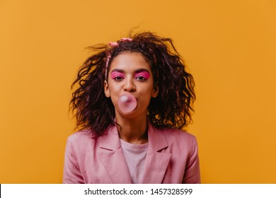 Dark-eyed girl with pink makeup chewing bubble gum. Studio photo of relaxed african lady isolated on yellow background.