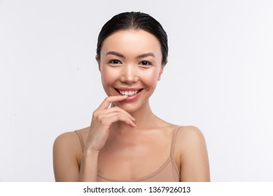 Dark-eyed woman. Dark-eyed appealing young woman wearing beige camisole smiling broadly