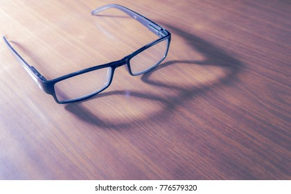 Dark-framed reading eye wear on a wooden surface, decorated by not very intense shadow and soft light.