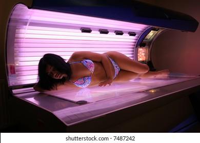 Dark-hair girl tanning in solarium.