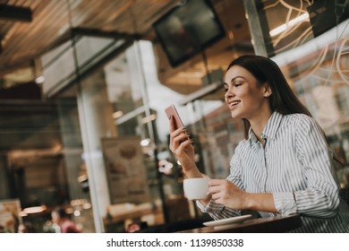 Dark-haired and beautiful woman is sitting at the table and looking at phone. She is smiling. Girl has cup of cofffee on right hand. She is sitting in restaurant