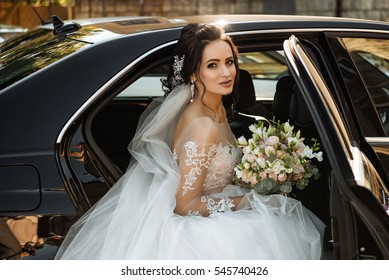 dark-haired bride jewelry head sits in a black car on your wedding day with a bouquet. Portrait of the bride. fluffy white lace dress