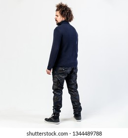 Dark-haired curly guy with a beard in a black turtleneck, khaki pants and sneakers poses in the studio on the white background.