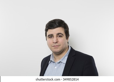 Dark-haired european businessman with a funny look stares into the camera while in front of a gradient background