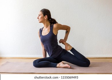 A dark-haired European woman in her 30's practices yoga at home. Meditation, stretching and mindfulness to achieve physical and spiritual health.
