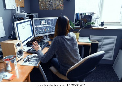 Dark-haired Female Sits At Office Table Surrounded By Technics And Works In Video Editor. Girl Is Passionate About Working At Computer. Lipik's Stock Media office. May 2019. Kyiv, Ukraine.
