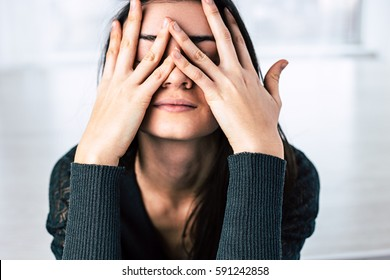 Dark-haired girl covers her face with hands