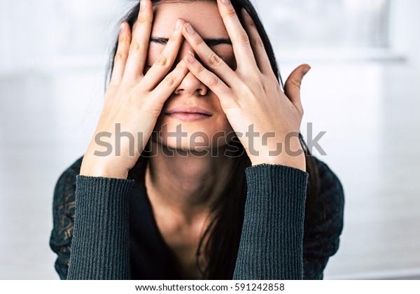 黒髪の女の子が手で顔を覆う