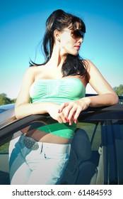 dark-haired girl in glases near the car