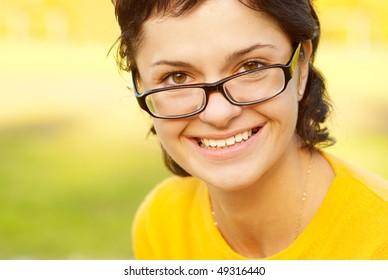 Dark-haired girl in glasses against autumn.